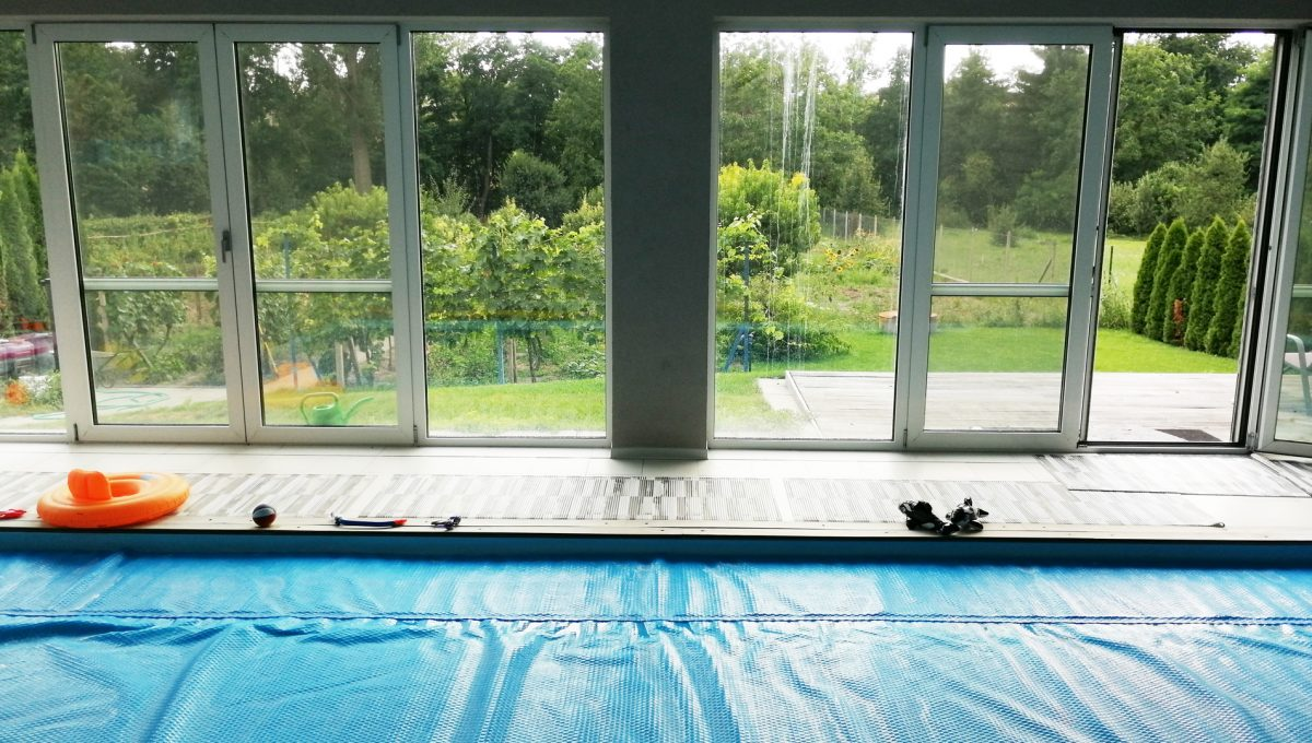 Blatne 08 Senec velky rodinny dom velky pozemok pohlad spoza bazena cez presklenenu stenu na velmi peknu a udrziavanu zahradu za rodinnym domom